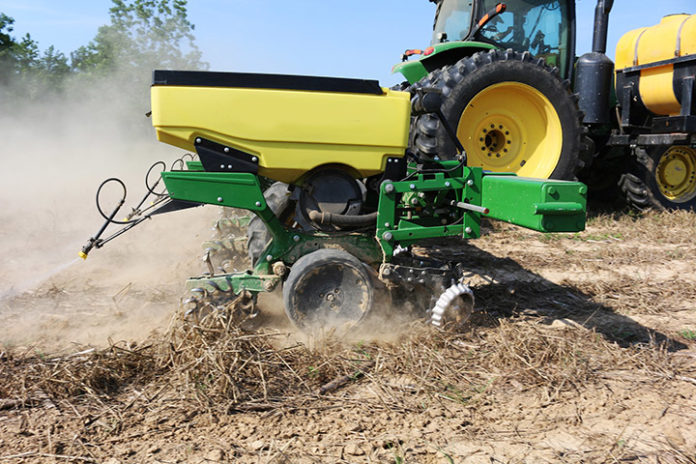Tractor and tillage implement tilling soil.